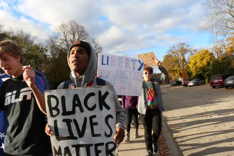 """Rockim Williamson '18 holds a """"Black lives matter"""" sign during the unity rally."""