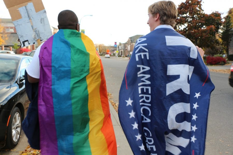 Student wrapped in pride flag and student wrapped in Trump flag walk side by side.   All photos by Riley Lynch '18