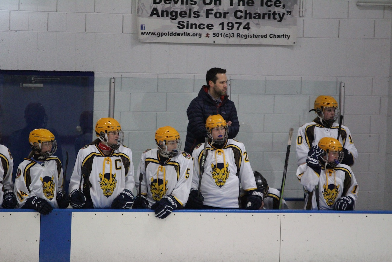 The girl's hockey team preparing for a game. The coach, Christopher Booth, has a passion for teaching and finds coaching to be especially rewarding.