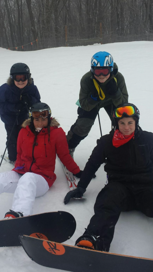 Ulku '19 poses in the winter snow while snowboarding with friends and family.