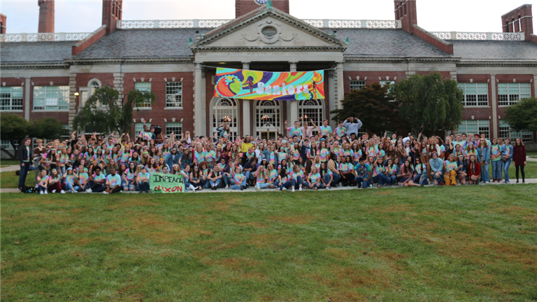 The+class+of+2019+poses+on+the+front+lawn+for+their+final+spirit+day+photo.