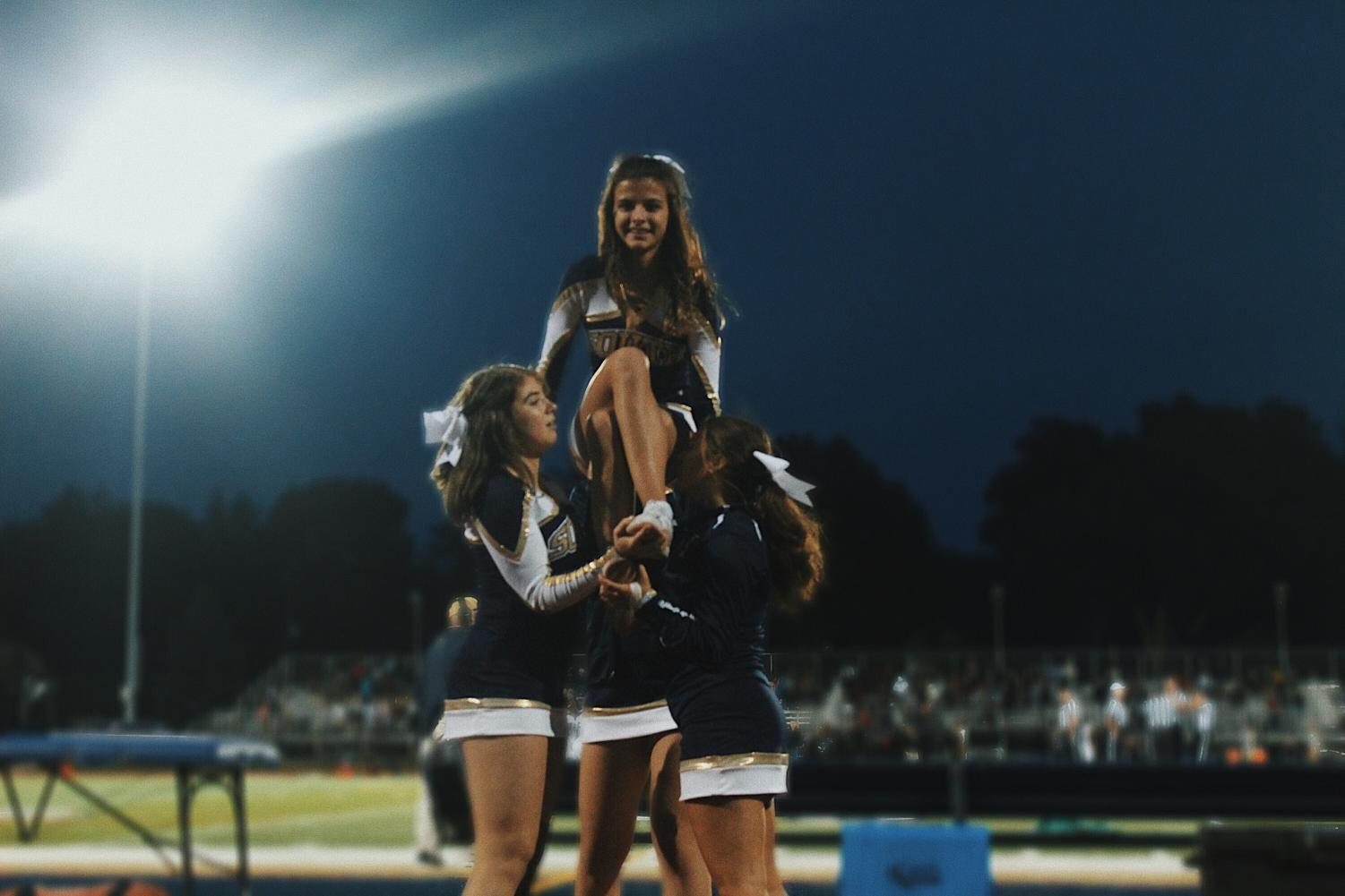 The cheerleader team performing a stunt. Photo courtesy of Anne Muawad '20.