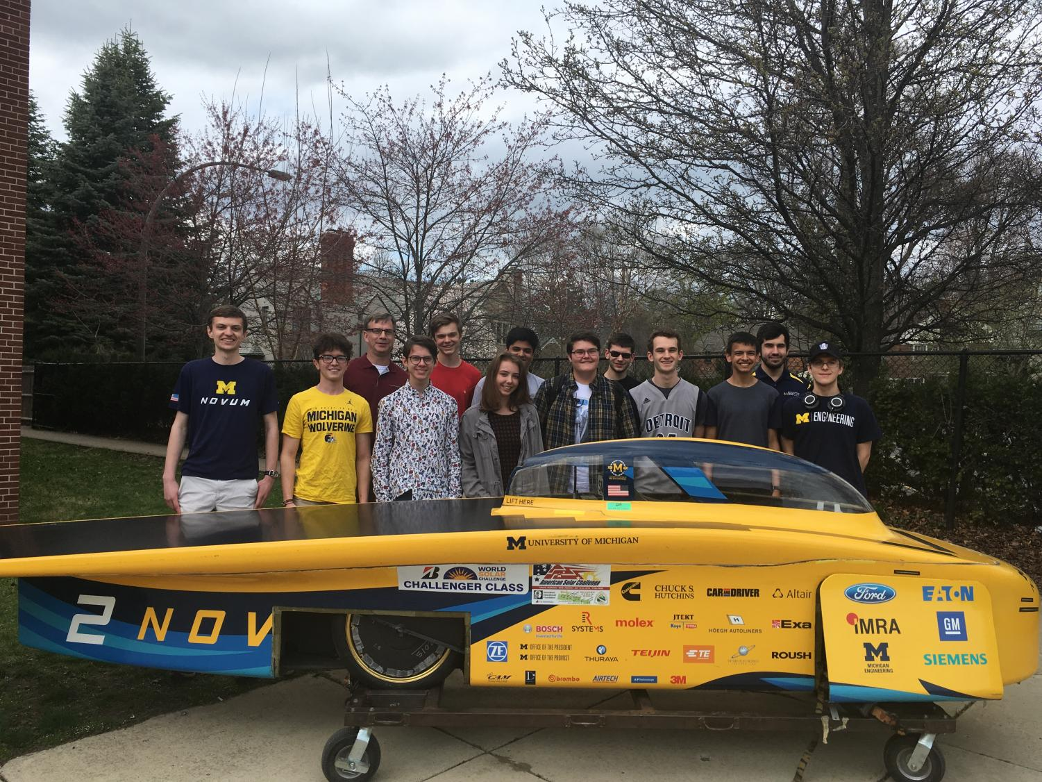 The team, whose ultimate goal is to build a car using only solar power, stands with the University of Michigan's solar car last year. The team has raised $30,000, $5,000 more than their initial goal. Photos courtesy of Alex Bower '20.