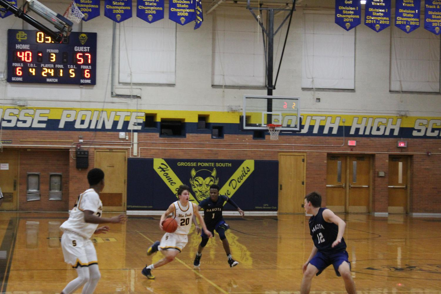 Alex Shaheen '20 dribbles up the court last season against Dakota. The team is under a new coach this season and Shaheen said the team is looking to beat cross-town rival North twice. Photo by Ryan Caldwell '21.