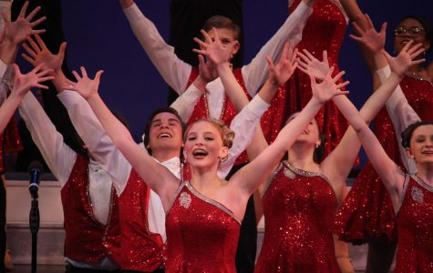 """FINALE The South Singers, including Hannah Gunnell '23 (center), raise their arms in the final pose from their rendition of """"Raise You Up/Just Be"""" from the musical """"Kinky Boots"""". This medley, along with four other numbers curated by choir director Christopher Pratt, helped the South Singers secure a spot in the finals of the Bishop Luers Midwest Show Choir Invitational  for the first time in the program's history."""