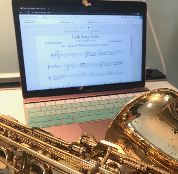 """MUSIC THROUGH THE SCREEN Students have been using SmartMusic, a website that allows the students to play a song with a recording and submit it to their teachers. """"Unfortunately, it isn't a perfect substitute for real-life ensembles, but it's probably the best we have under these circumstances,"""" alto-saxophone player Emilia Cywinski '22 said. Photo Courtesy of Emilia Cywinski."""